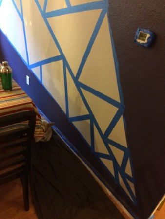 Dining room wall taped in triangular pattern in preparation for painting.